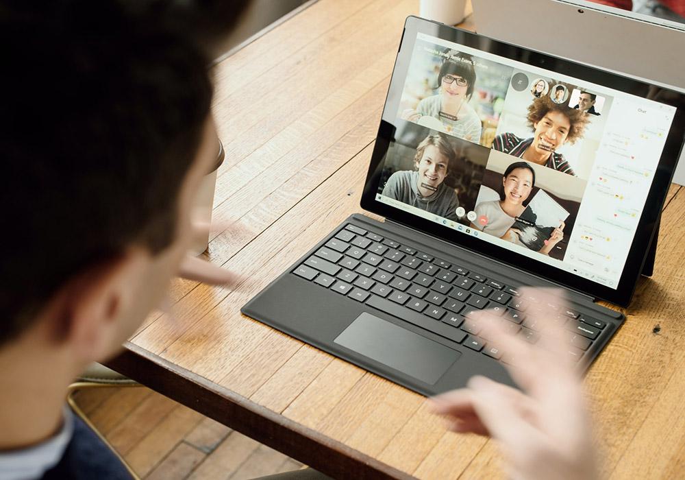 Ein Mann arbeitet an seinem Laptop. Auf seinem Bildschirm sind vier weitere Personen zu se-hen, die mit ihm gemeinsam an einer Videokonferenz teilnehmen.