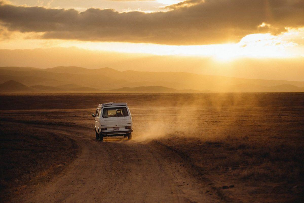 Ein VW-Bus ist von hinten zu sehen, wie er auf einer staubigen Piste dem Sonnenuntergang entge-genfährt.
