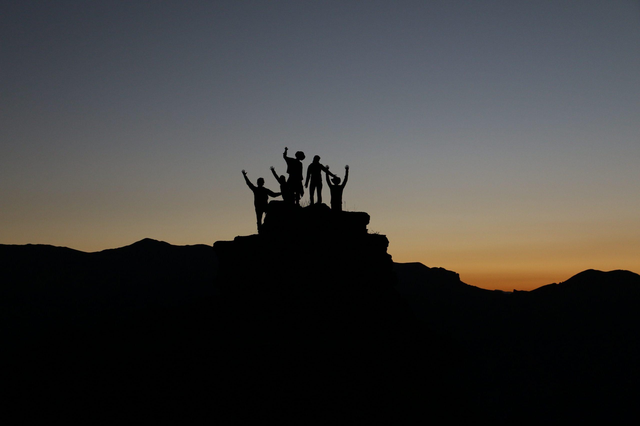 Ein 5-köpfiges Team erklimmt in der Abenddämmerung einen Berggipfel und feiert gemeinsam seinen Erfolg. Die Szene ist nur als Silhouette zu sehen und die Personen reißen freudig die Arme in die Höhe.